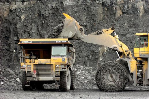 A digger loads large rocks from the pit floor onto a truck at the CRH Plc. quarry in west Dublin. Photo: John Cogill/Bloomberg News.