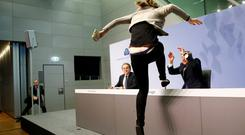 A protester jumps on the table in front of the European Central Bank President Mario Draghi during a news conference in Frankfurt. Photo: Reuters