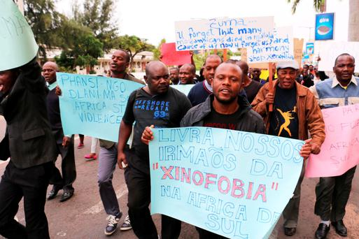 "A demonstrator holds a banner that reads ""Free our brothers from the xenophobia in South Africa""."