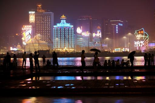 People walk on a water front near a strip of casinos including the Wynn, and the older Hotel Lisboa, at night in Macau.