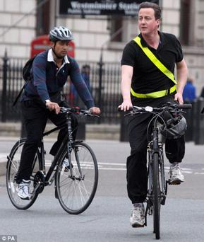 Pedal power: David Cameron, with a helmet dangling from the handlebars