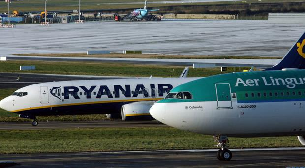 Aer Lingus and Ryanair aircraft sit on the runway at Dublin International Airport