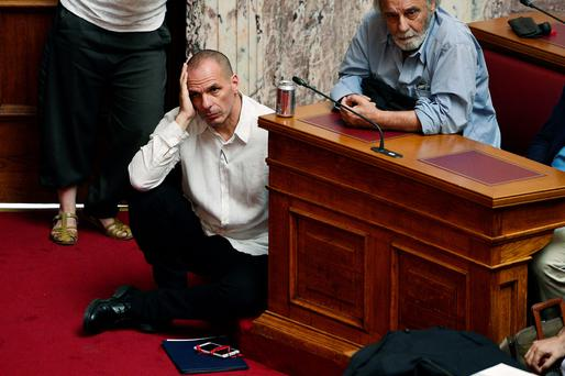 Finance Minister Yanis Varoufakis listens to Prime Minister Alexis Tsipras addressing MPs in the Greek parliament in Athens yesterday