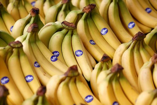 Bunches of Fyffes bananas sit displayed for sale on a fruit and vegetable stall at an outdoor market