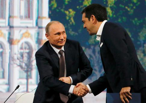 Russian President Vladimir Putin (L) shakes hands with Greek Prime Minister Alexis Tsipras during a session of the St. Petersburg International Economic Forum 2015 (SPIEF 2015) in St. Petersburg, Russia, June 19, 2015. Greece's debt crisis is a problem for