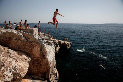 A bather leaps from a rock into the sea on the coast south west of Athens, Greece