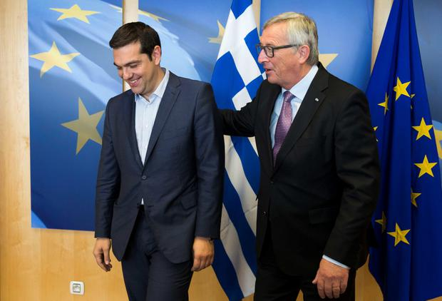 Greece's Prime Minister Alexis Tsipras (L) is welcomed by European Commission President Jean-Claude Juncker (R) ahead of a meeting on Greece, at the European Commission in Brussels, on June 24