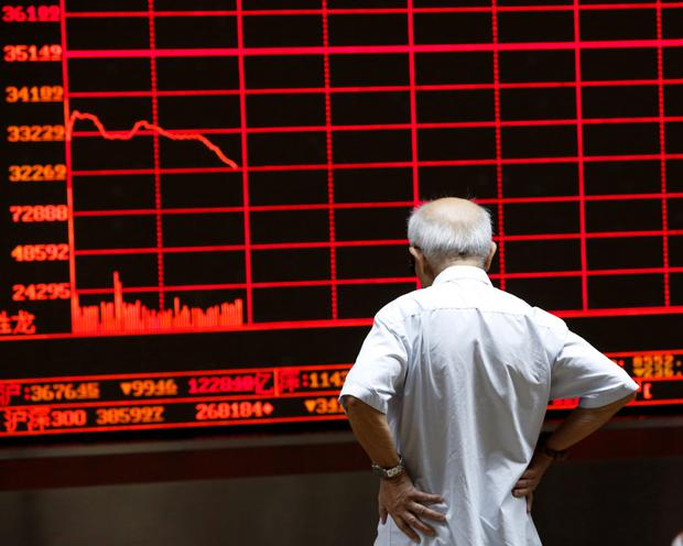 An investor watches an electronic board showing stock information at a brokerage office in Beijing, China, July 7, 2015
