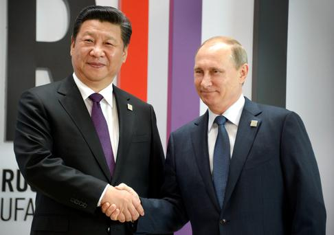 Russia's President Vladimir Putin (R) greets China's President Xi Jinping during a welcome ceremony in Ufa on July 9, 2015 at the start of the 7th BRICS summit