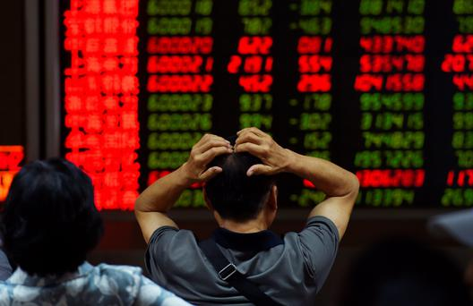 An investor looks at screens showing stock market movements at a securities company in Beijing on July 14, 2015. Hundreds of firms were expected to resume trading again on July 14, adding to the more than 400 that returned July 13, after they were suspended over the past few weeks to prevent a market meltdown. Authorities intervened after the Shanghai index plunged 30 percent in three weeks, wiping trillions of dollars from