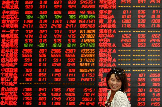 An investor smiles as she walks past an electronic board showing stock information at a brokerage house in Fuyang, Anhui province, China, July 17, 2015. China stocks closed up on Friday, overcoming a mid-week slide to end up for a second week, with market insiders saying the