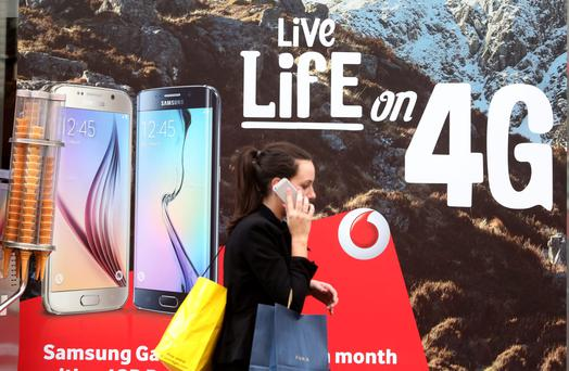 A pedestrian talks on her mobile phone device as she walks past a Vodafone advertisement outside a store, operated by Vodafone Group Plc, in London, U.K., on Friday, June 5, 2015. Vodafone Group Plc said it was in talks to exchange assets with billionaire John Malone's Liberty Global Plc in a deal between two of Europe's biggest wireless and cable providers. Photographer: Chris Ratcliffe/Bloomberg