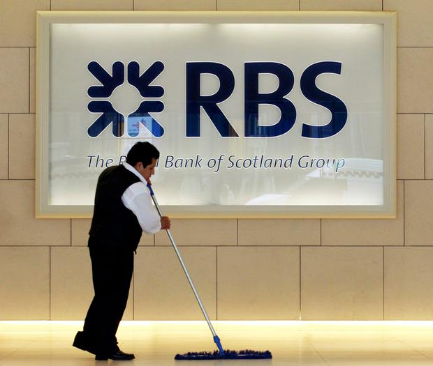 A worker sweeps in the foyer of a Royal Bank of Scotland office in the City of London in this file photo dated August 6, 2010. Britain started to return its holding in Royal Bank of Scotland to private investors on Monday, seven years after it bailed out t
