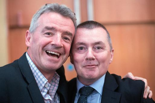Michael O'Leary, chief executive officer of Ryanair Holdings Plc., Europe's biggest discount carrier, and Willie Walsh, chief executive officer of International Consolidated Airlines Group SA (IAG), the parent of British Airways PLc., pose for a photograph during a break during the Airport Operators Association (AOA) annual conference in London, U.K., on Tuesday, Oct. 22, 2013.