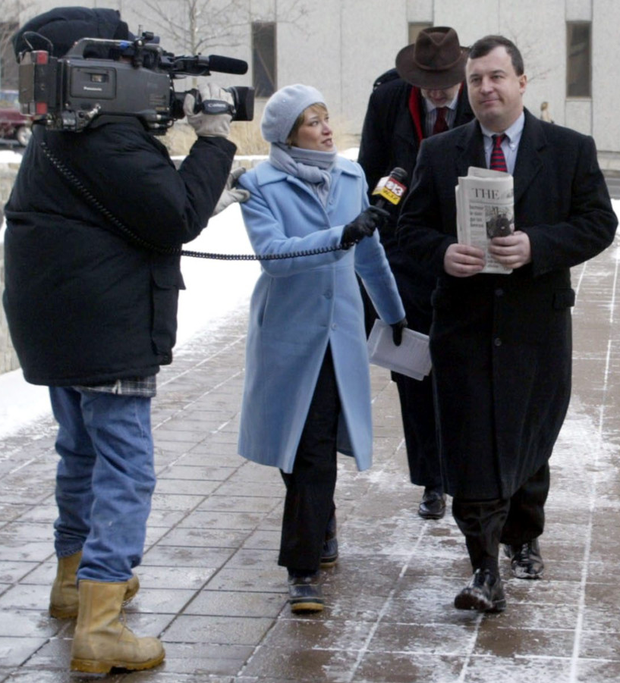 A local television crew questions John Rusnak (holding paper), former Allfirst foreign currency trader, as he arrives at the US Courthouse in Baltimore, Maryland, in 2003. Mr Rusnak served six years in prison for bank fraud.