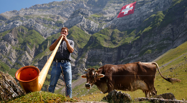 A man plays a traditional alphorn as a huge Swiss national flag is seen on the landmark Mount Saentis for the country's recent national day