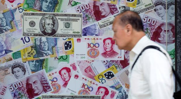 A man walks past yuan signs at a currency exchange in Hong Kong. REUTERS/Tyrone Siu