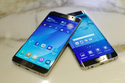 A Samsung Electronics Co. Galaxy S6 Edge Plus smartphone, right, and a Galaxy Note 5 smartphone sit on a surface in London, U.K., on Tuesday, July 28, 2015. Samsung unveiled bigger-screen versions of the S6 and Note smartphones featuring its own mobile-pay
