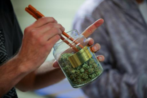 An employee pulls marijuana out of a large canister for a customer at the LoDo Wellness Center in downtown Denver, Colorado, U.S., on Thursday, Jan. 9, 2014. Colorado has just legalized the commercial production, sale, and recreational use of marijuana, while Washington State will begin its own pot liberalization initiative at the end of February. On Jan. 8, New York Governor Andrew Cuomo said his state would join 20 others and the District of Columbia in allowing the drug for medical purposes. Photographer: Matthew Staver/Bloomberg