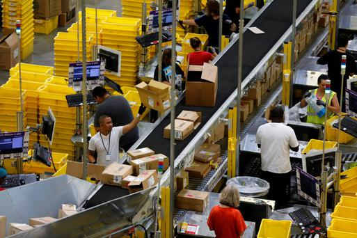 Workers sort arriving products at an Amazon Fulfilment Centre in Tracy, California