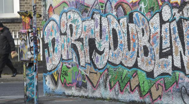 A man walks past graffiti daubed on the wall of the Windmill Lane Studios, belonging to the band U2, in central Dublin. Photo: Niall Carson/PA Wire...A