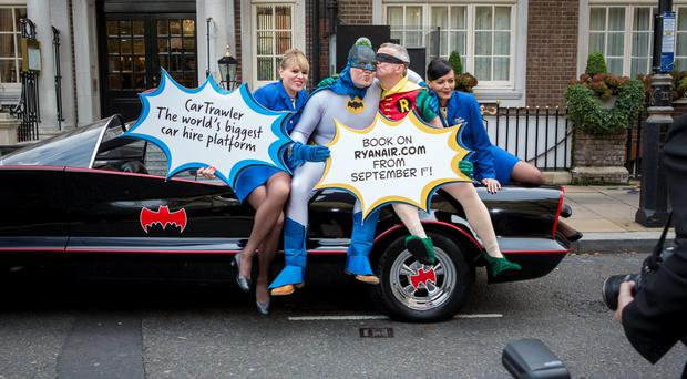 Ryanair CEO Michael O'Leary dressed as Robin and Car Trawler CEO Mike McGearty dressed as Batman kiss to seal the deal.