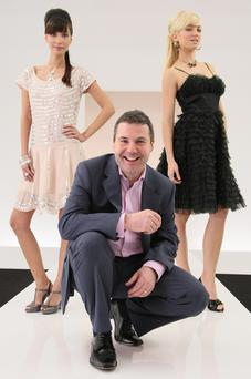 Nick Robertson, outgoing chief executive officer of internet retailer Asos, poses with models Mariel Booth and Elodie Bonis