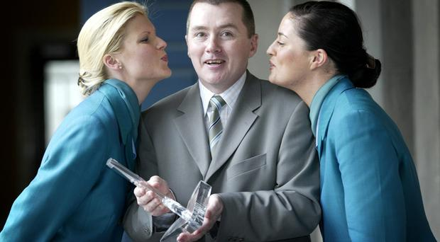 Willie Walsh pictured picking up an airline award at an event with Aer Lingus cabin crew in 2003