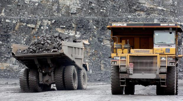 Lorries remove rocks from the pit floor at a CRH quarry