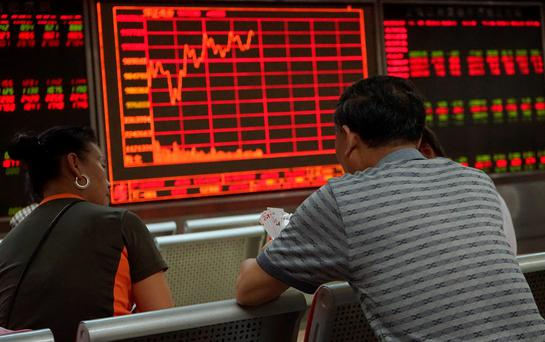 Investors play cards in front of an electronic board showing stock information in Beijing