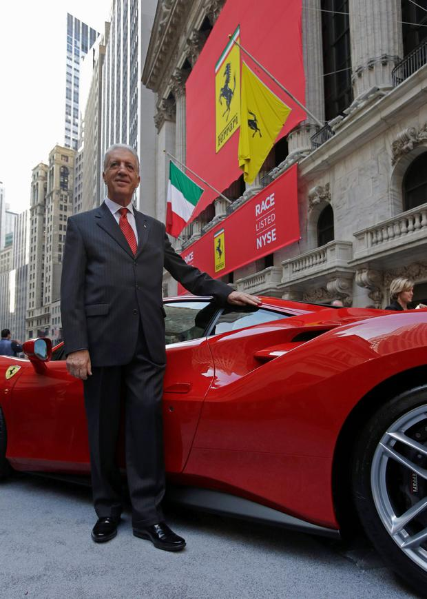 Piero Ferrari, Vice-Chairman of Ferrari, poses with a Ferrari sports car outside the New York Stock Exchange October 21, 2015. Shares in Ferrari rose 15 percent to $60 in the luxury group's Wall Street debut on Wednesday after it priced its share offering