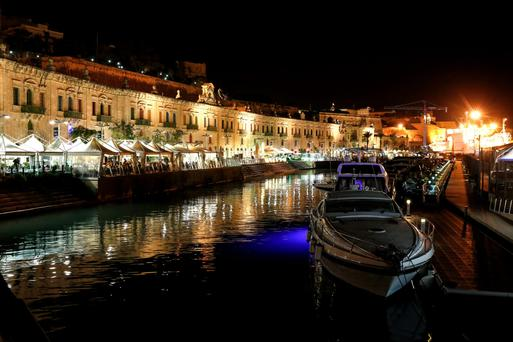 Restaurants and bars line the waterfront district at night in Valletta, the capital of Malta