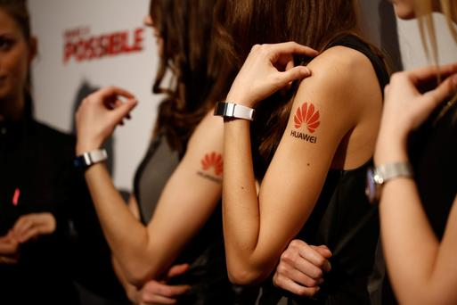 Employees demonstrate the new Huawei TalkBand B2 wearable devices during a Huawei Technologies news conference ahead of the Mobile World Congress in Barcelona. Photo: Bloomberg