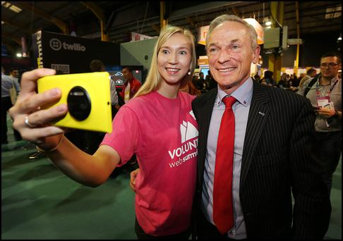 Minister for Jobs, Enterprise and Innovation Richard Bruton attending at the Web Summit at the RDS gets a selfie with Volunteer Netta Huttunen from Finland.
