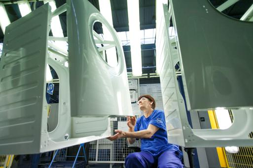 A worker examines washing machines on an Electrolux assembly line. Photo: Bloomberg