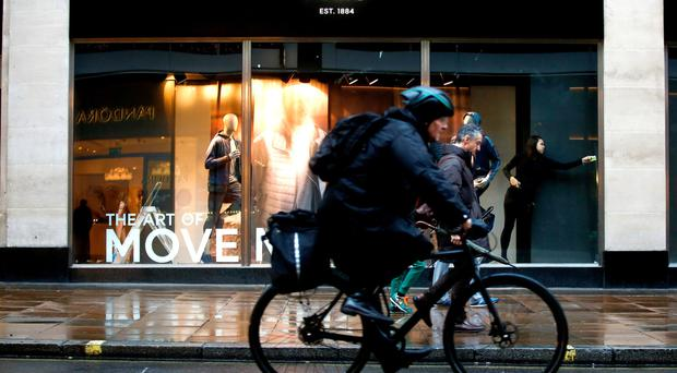A cyclist rides past a display window at a Marks And Spencer Plc store on Oxford Street in London