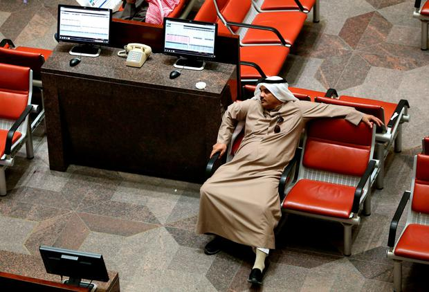 A Kuwaiti trader follows the stock market activity at the Kuwait Stock Exchange in Kuwait City as share prices in the energy-rich Gulf states nosedived yesterday amid chronic oil concerns. Photo: AFP/Getty Images