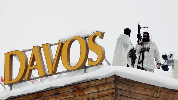 Swiss special police officers observe the surrounding area from the roof of the Davos Congress Hotel yesterday. Photo: Reuters
