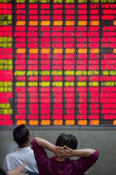 Investor look at an electronic board displaying share prices at a securities exchange house in Shanghai, China.
