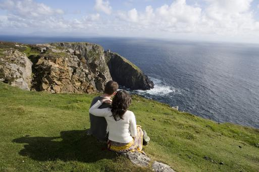 A couple sit and watch the ocean crash into the sea cliffs at Slieve League in Co Donegal, on the northern part of the Wild Atlantic Way