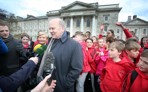 Acting ministers Michael Noonan and Frances Fitzgerald of Fine Gael speaking to the media on arrival for the talks with Fianna Fáil on the formation of a minority government in Trinity College this week. Behind are pupils of Scoil na nÓg,Glanmire, Cork. Photo: Tom Burke