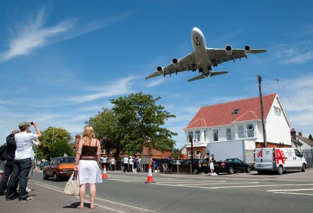 An Airbus A380 aircraft on landing approach over a local suburban street at the world's biggest airshow, in Farnborough