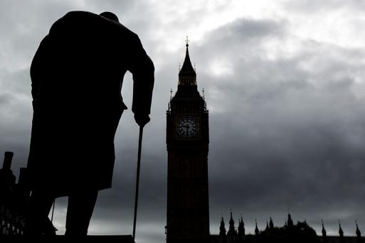 The statue of Winston Churchill stands silhouetted in Parliament Square in London
