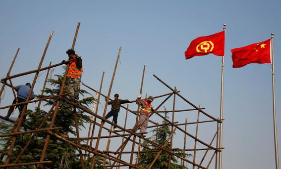 Workers build a wooden scaffolding outside the headquarters of the Bank of China in Beijing, China. Photo: Reuters