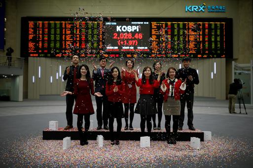 Employees of the Korea Exchange (KRX) pose in front of the final stock price index for 2016. REUTERS