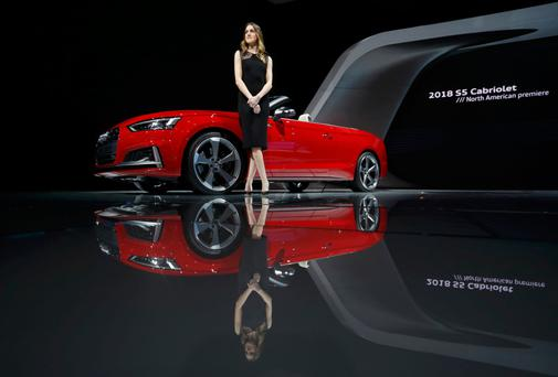 A model poses by a 2018 Audi S5 Cabriolet at the North American International Auto Show in Detroit