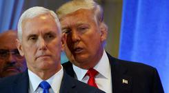 President-elect Donald Trump talks to vice president-elect Mike Pence during a news conference in the lobby of Trump Tower in New York during the week — Trump has pledged to target American pharmaceutical companies located overseas (AP Photo/Evan Vucci)