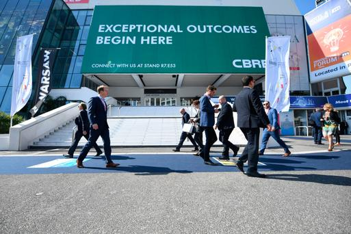 Visitors walk outside the entrance of MIPIM, an international real estate exhibition for professionals, at the Palais des Festivals in Cannes