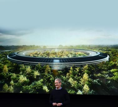 Apple CEO Tim Cook shows an image of the company's new HQ in Cupertino, California, which is due to open later this month