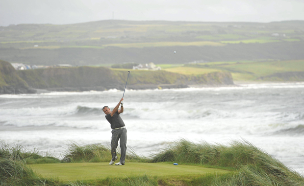 A golfer plays his tee shot from the 7th during the final round of the South of Ireland Amateur Open Golf Championship at Lahinchu